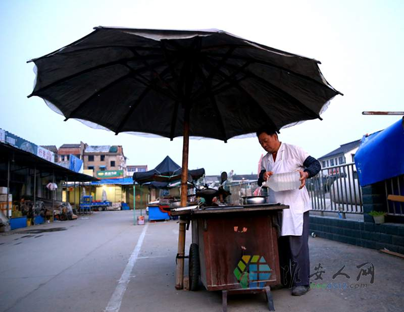 7 先撑起大伞 然后就忙开了 食客们从老远就能看到这巴大伞 就知武师傅的烧饼摊来了.jpg